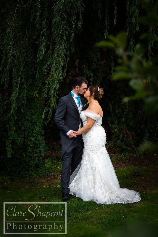 Groom and bride kiss outdoors under willow tree with blue tie