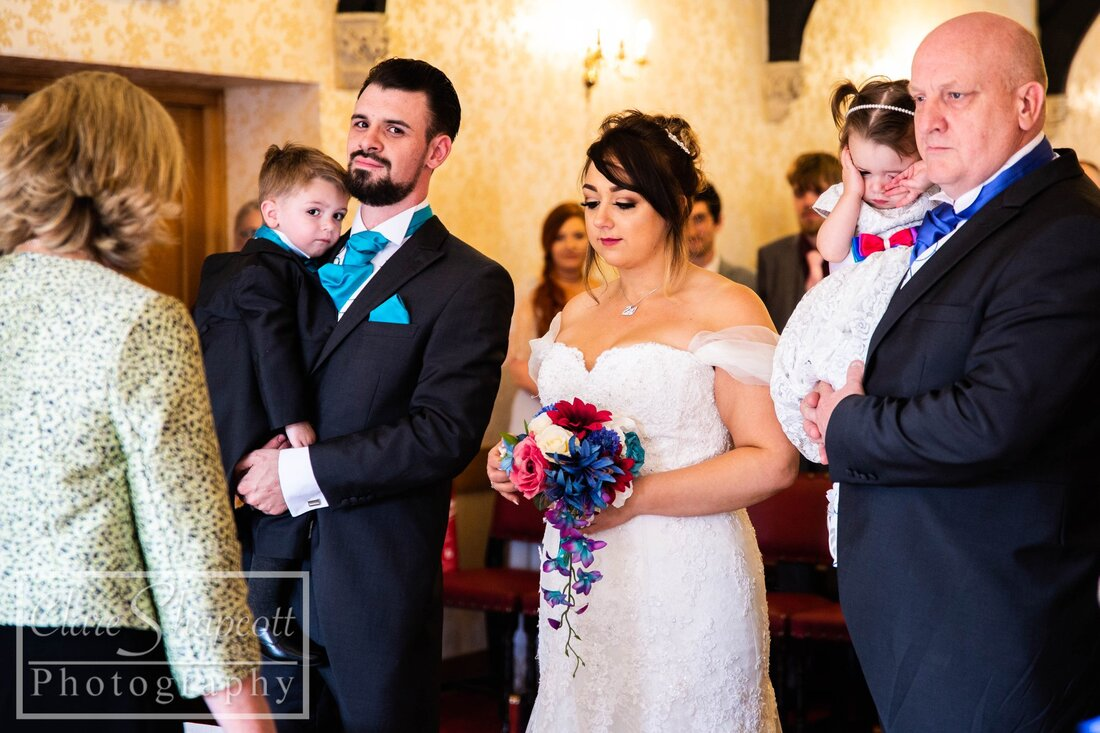 Bride and groom next to each other picking up son holding flowers at ceremony