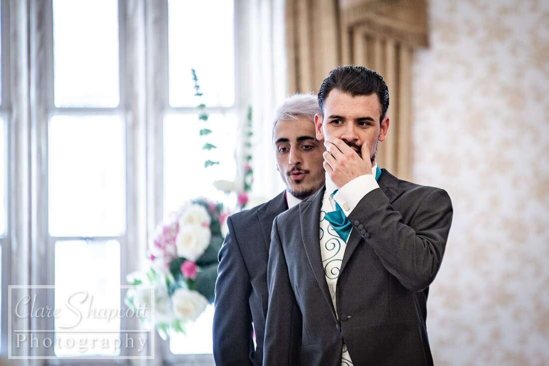 Groom excited to see bride holding hand to mouth next to best man