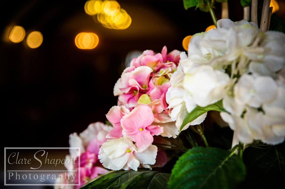 Close up photo of pink and white wedding flowers with leaves