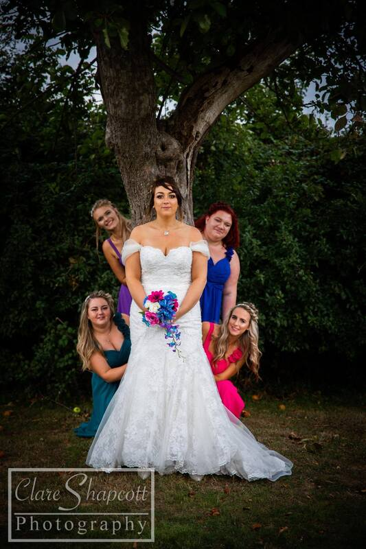 Bridesmaids poking out from behind tree in coloured dressed behind the bride