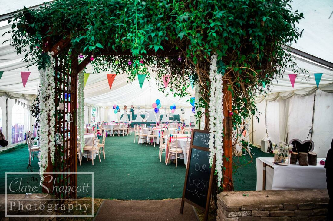Outdoor wedding reception in marquee with greenery on roof and bunting