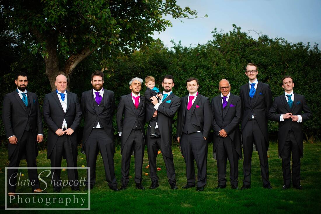 Groomsmen lined up outdoor for formal photograph with child in middle and rainbow ties