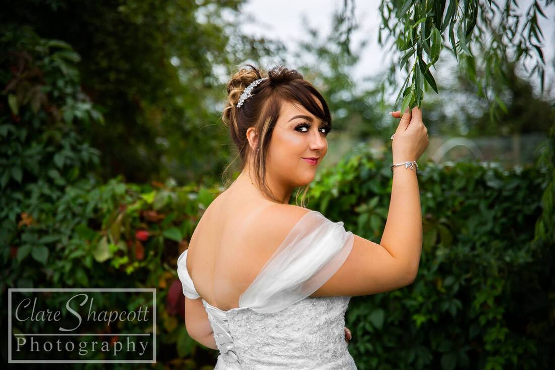 Close up of bride holding willow tree branch in front of bushes