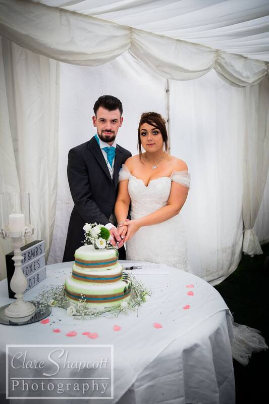 Clare Shapcott photography wedding cutting the cake in white marquee stripped cake