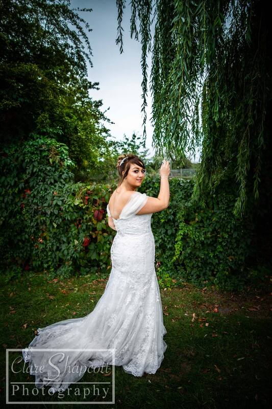 Outdoor wedding photograph of bride in white dress by herself holding willow branch and facing away