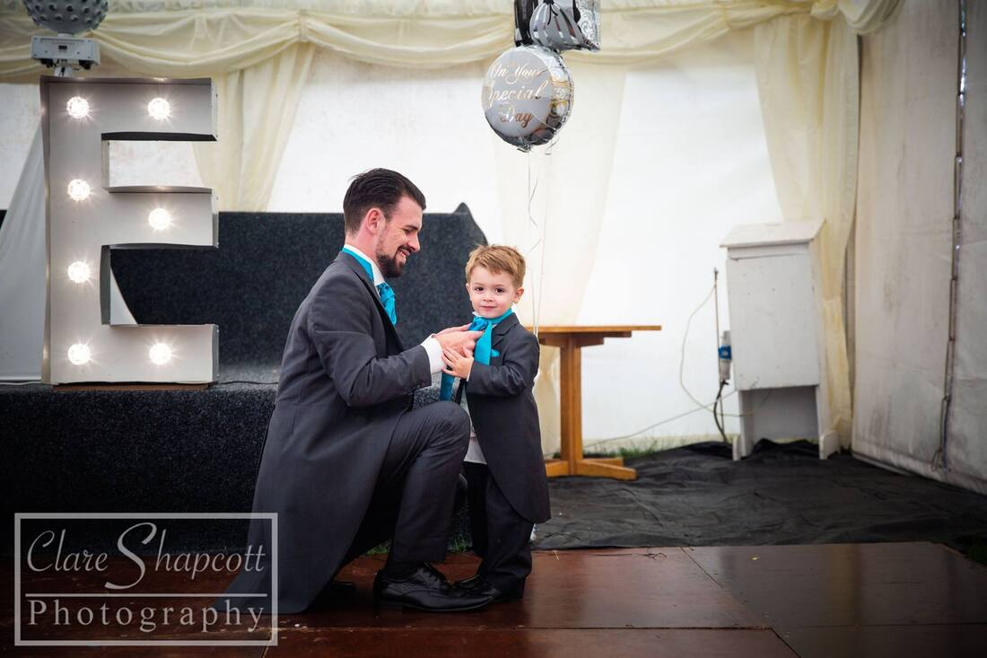 Groom knelt down to tie sons' blue tie at wedding reception