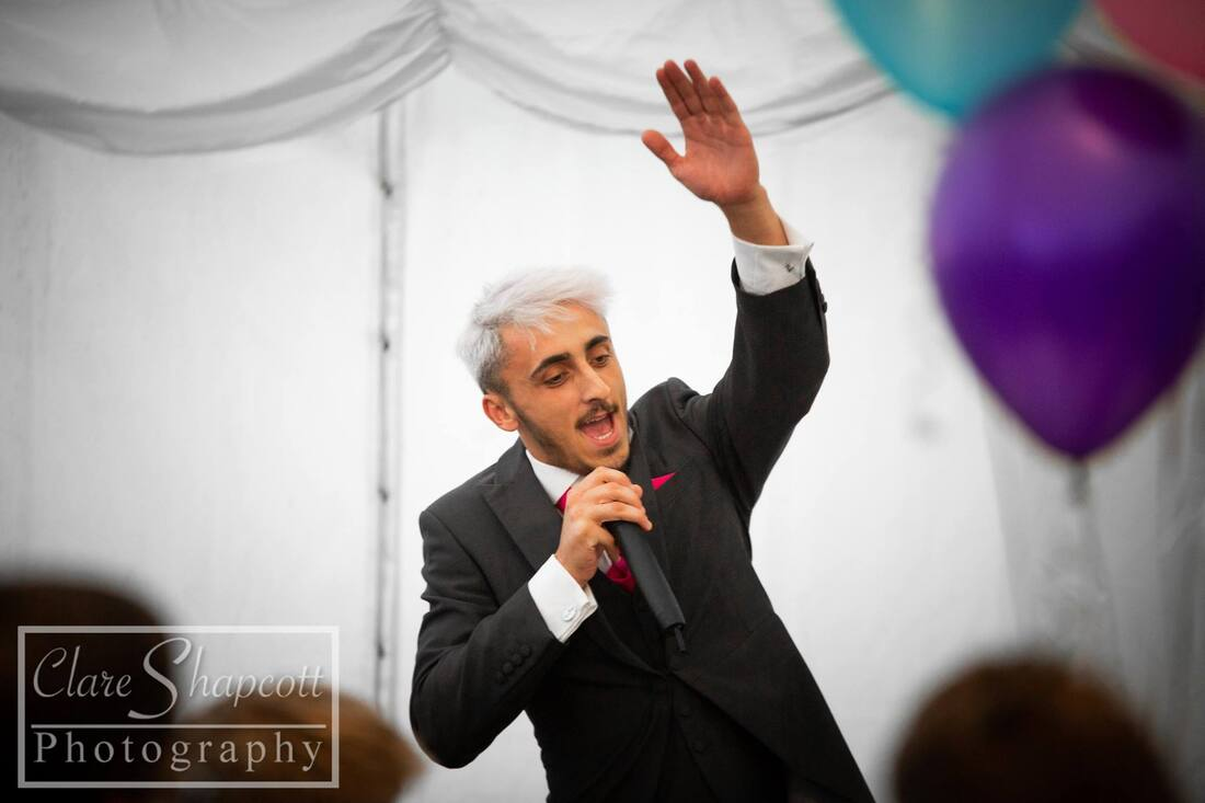 Best man with microphone and hand in air during speech next to purple balloon