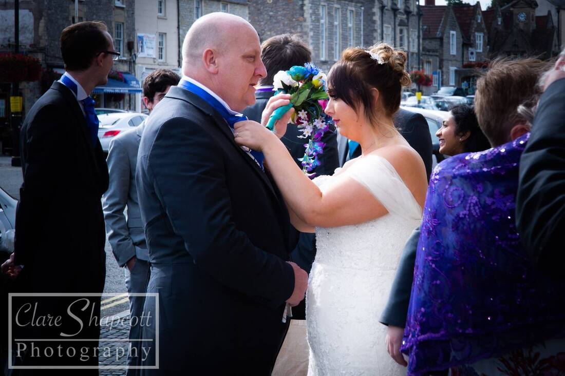 Bride adjusts father's suit outside on wedding day