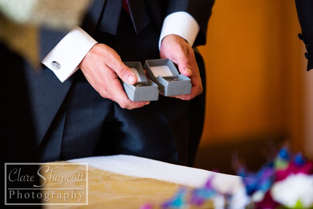 Best man presents wedding rings in boxes next to blurry flowers