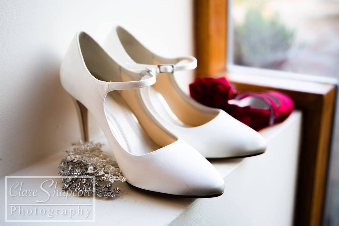 Photograph of white wedding high heeled shoes on ledge next to smaller red shoes