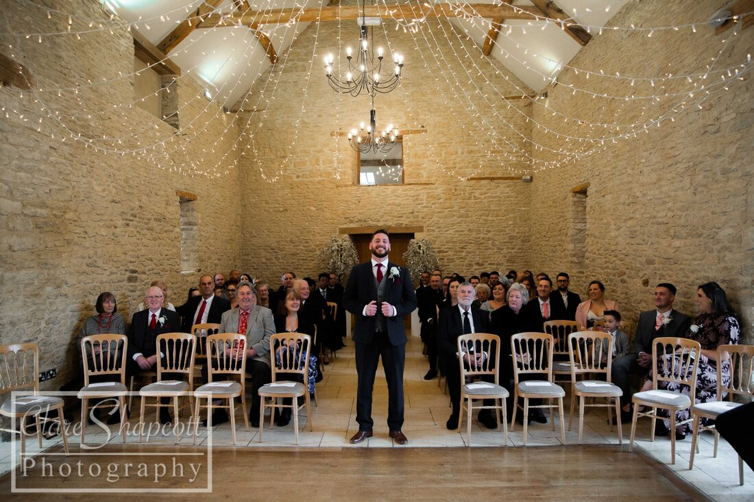 Groom waits for bride at wedding ceremony with guests and fairy lights
