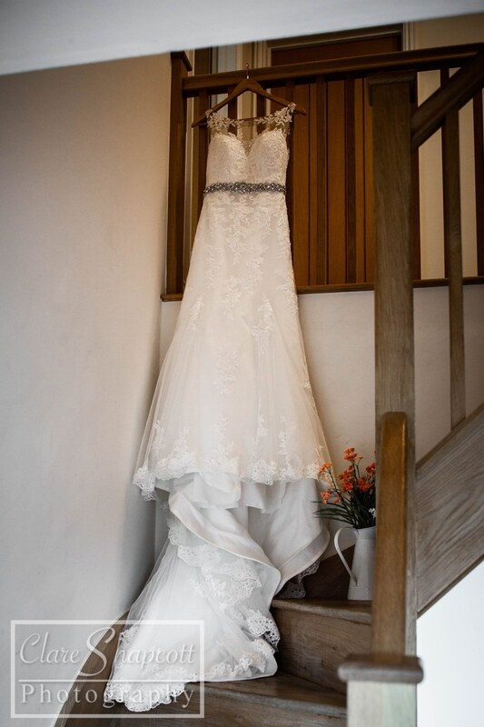White wedding dress hung up on stairs next to jug of orange flowers