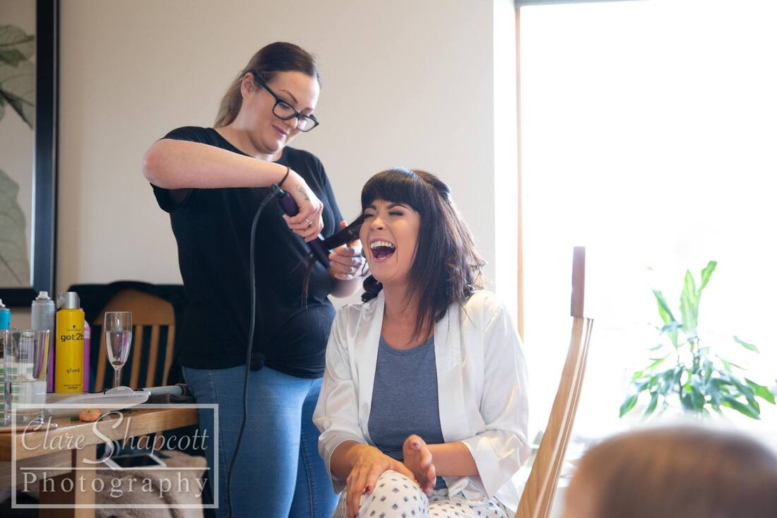 Woman laughs while having hair professionally styled before wedding