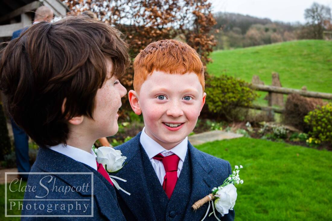 Young Groomsman looks at camera next to friend while outdoors