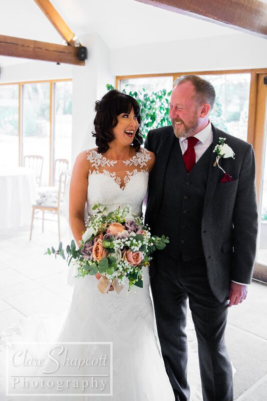 Bride and father smile at each other holding beautiful wedding flowers
