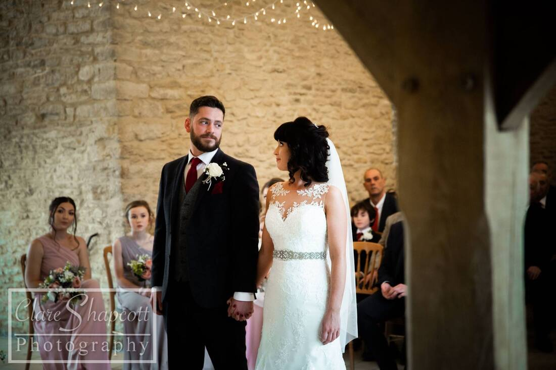 Groom holds bride's hand and they look at each other at ceremony with stone wall