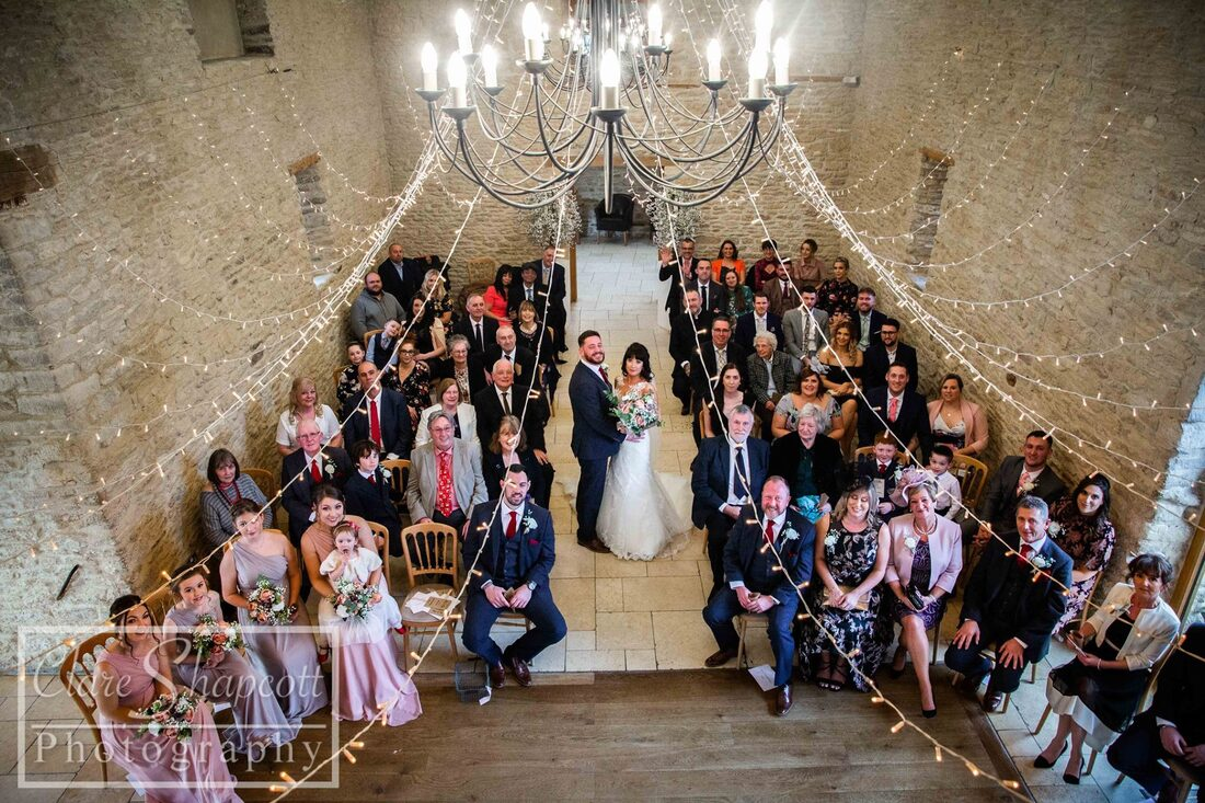 Professional wedding photograph from above of newly wed couple and guests below fairy lights
