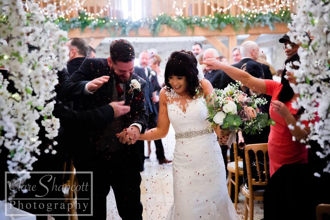 Guests throw confetti over bride and groom with white flowers on either side