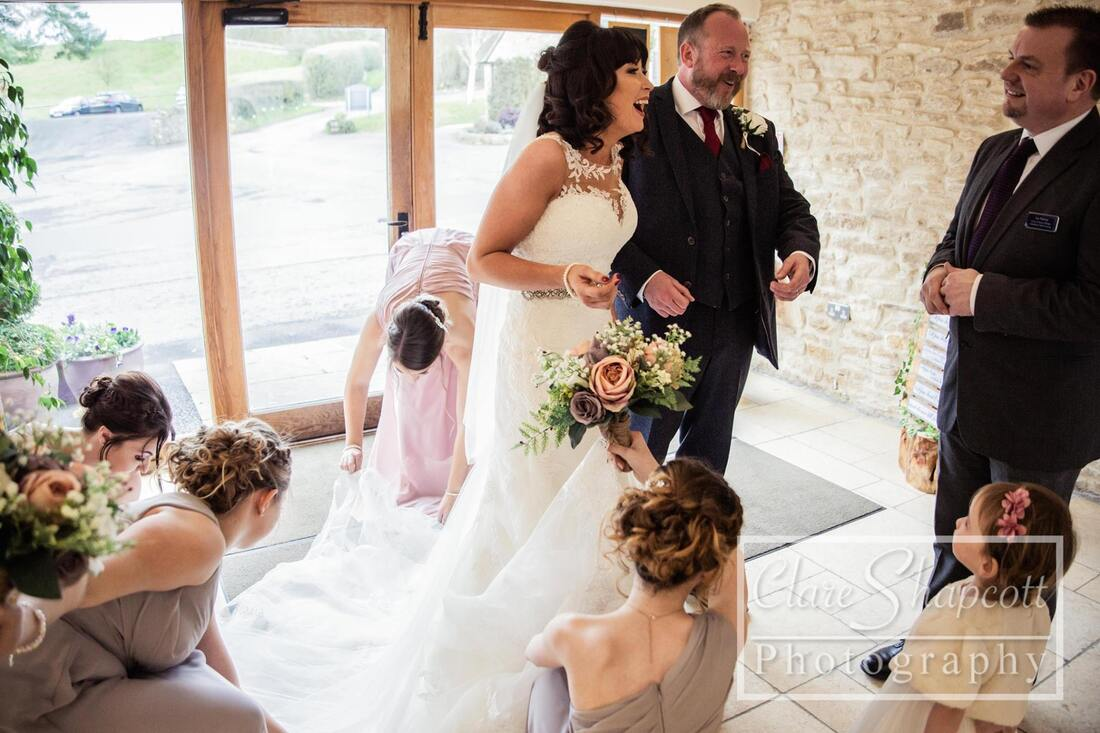 Bride laughs before wedding with bridesmaids sitting around her