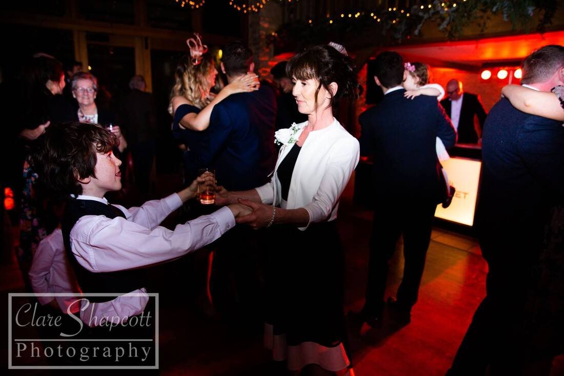 mother of bride dances with boy at wedding reception