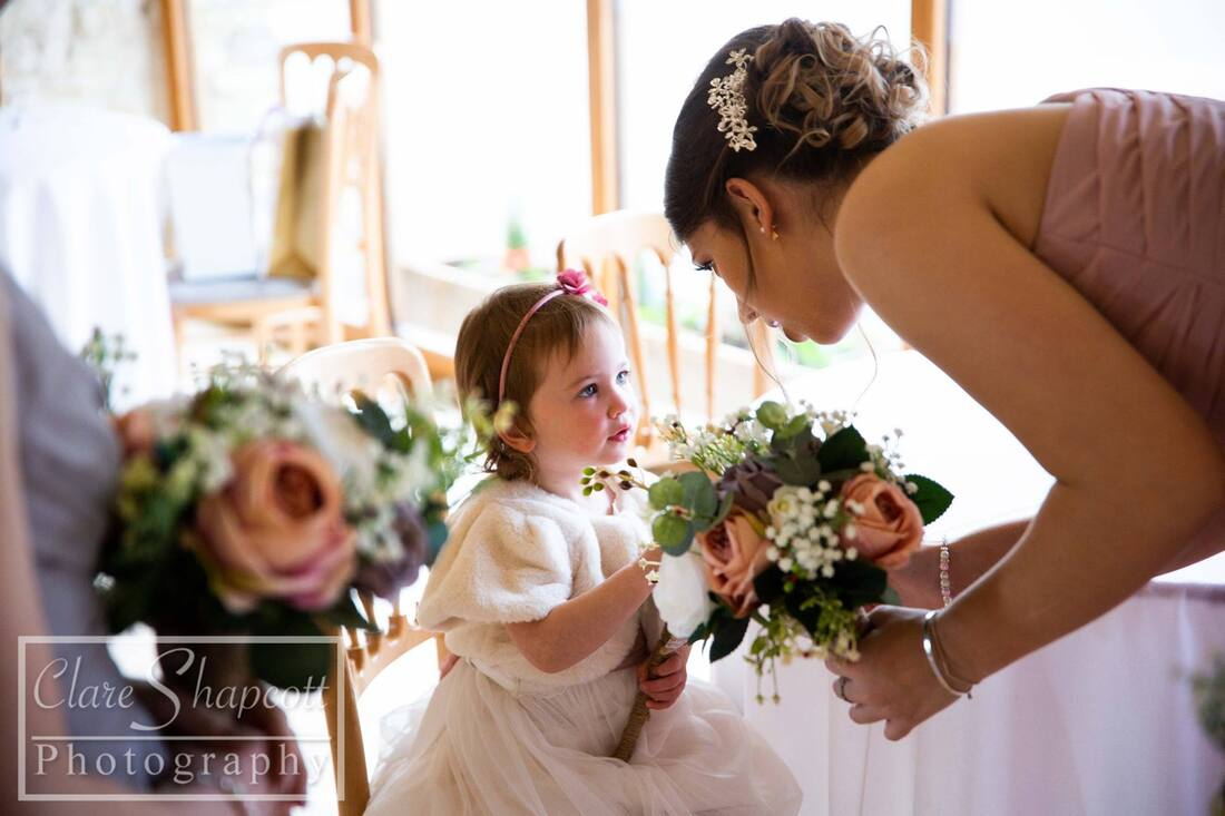 Young girl touching bridesmaids flower bouquet