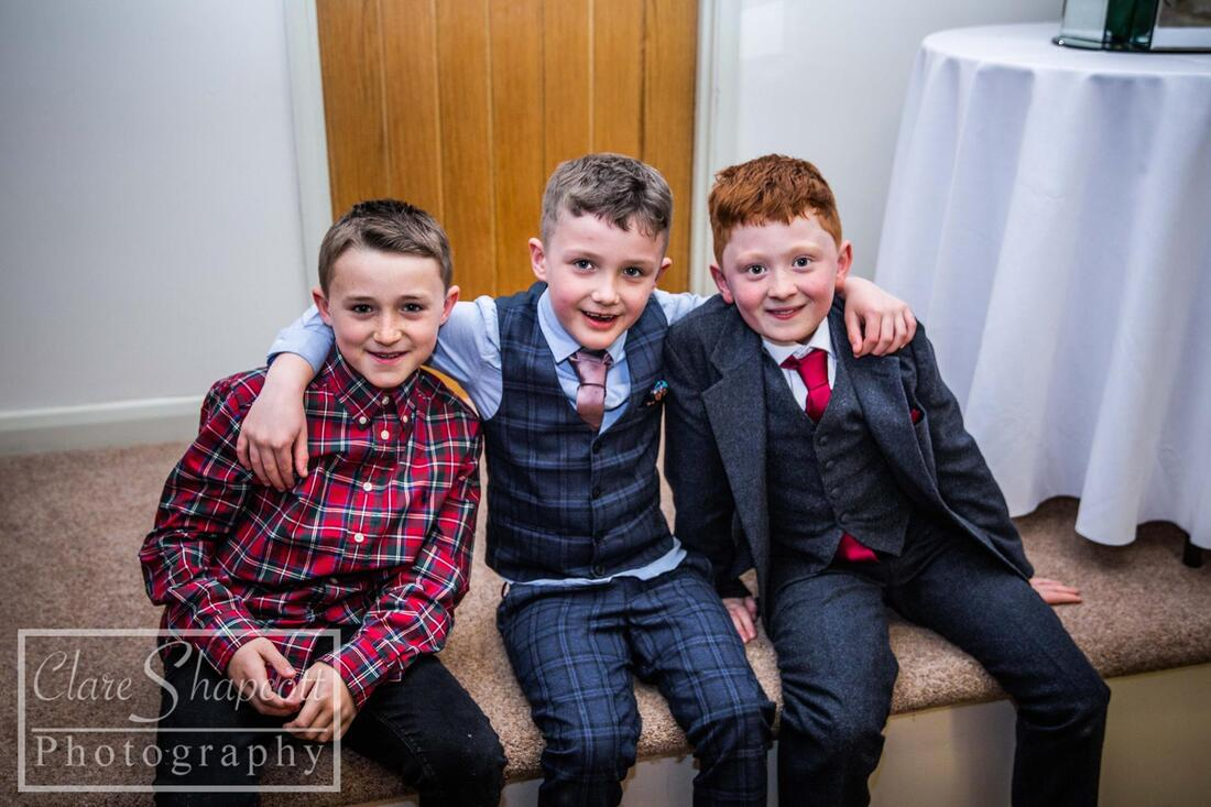 Three young boys with arms on shoulders at wedding smiling at camera