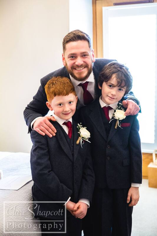 Groom with son and another boy smiling at camera with white buttonholes