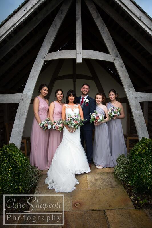 Bridesmaids surround bride and groom outside under archway for formal photograph