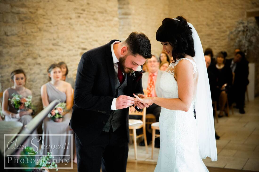 Groom puts on bride's ring at ceremony with bridesmaids behind