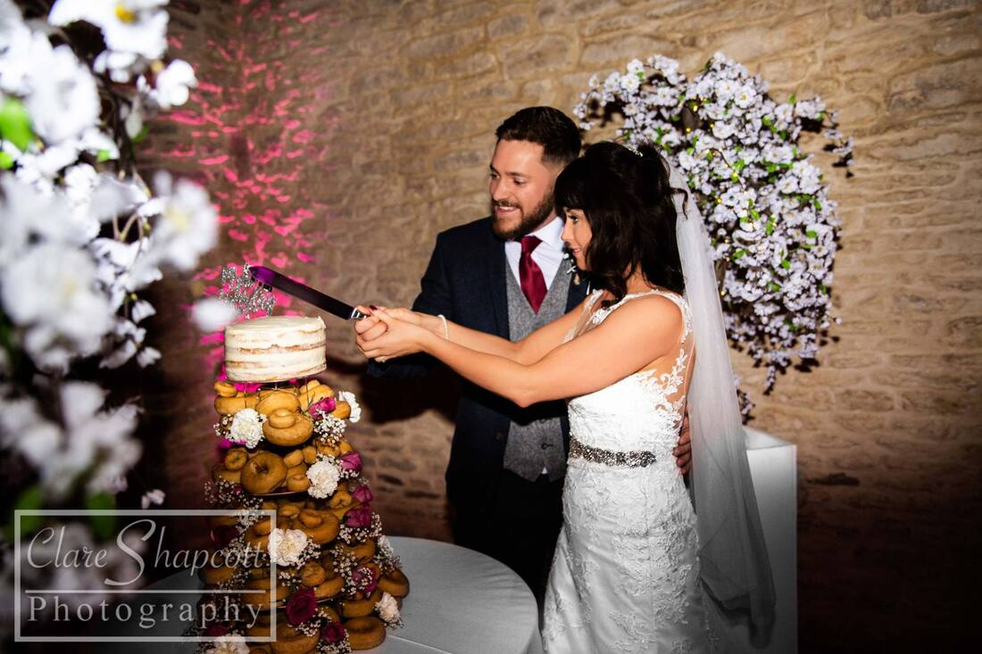 Bride and groom cut small white wedding cake with tower of doughnuts underneath