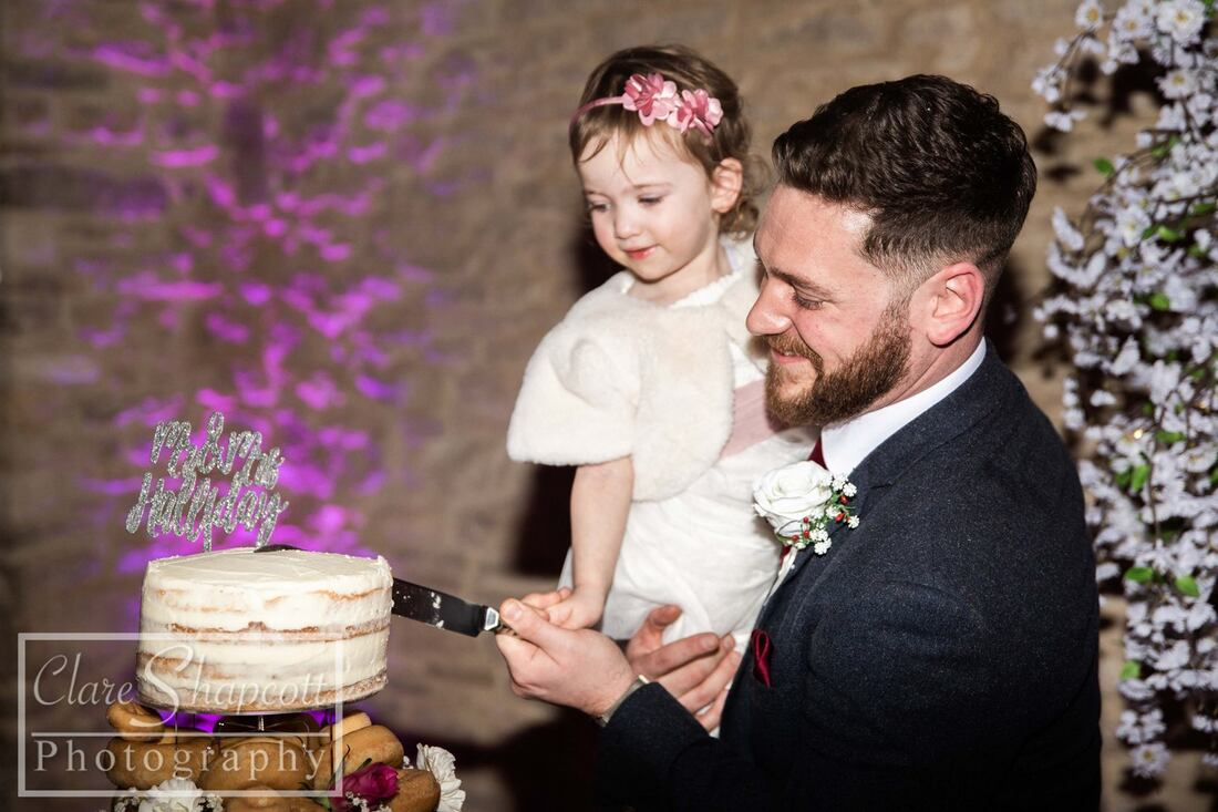 Groom cuts tiered wedding cake while holding daughter with pink headband and purple lights