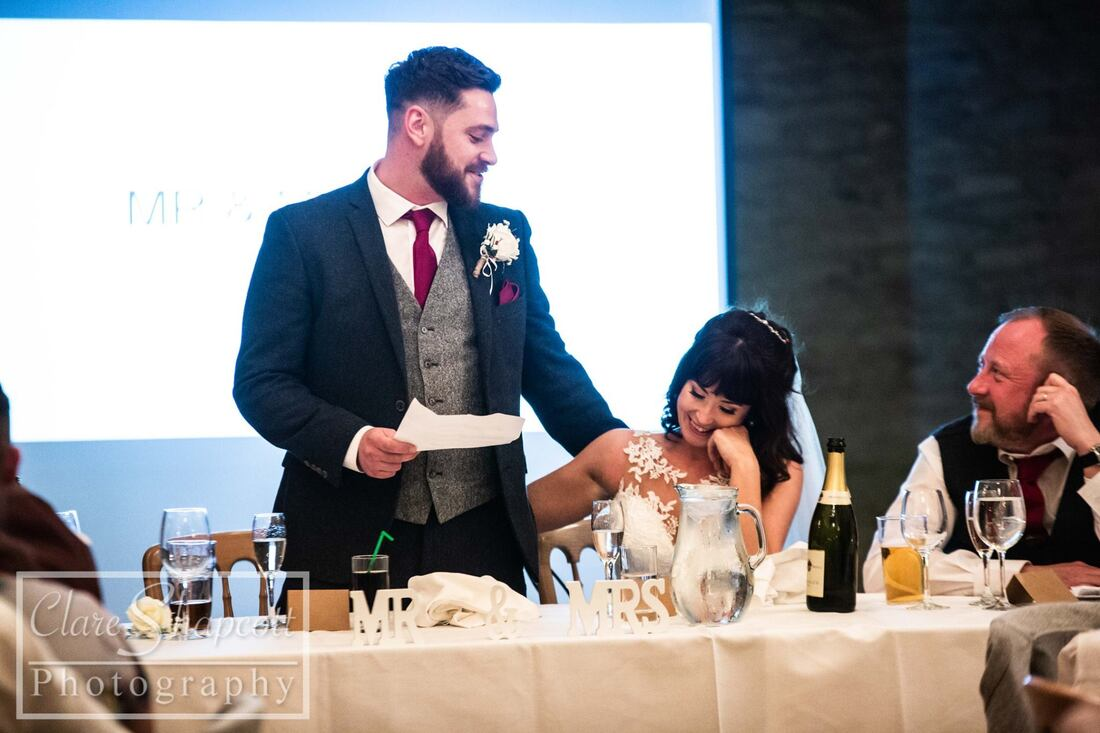 Groom making speech next to bride at table with drinks holding wife;s back