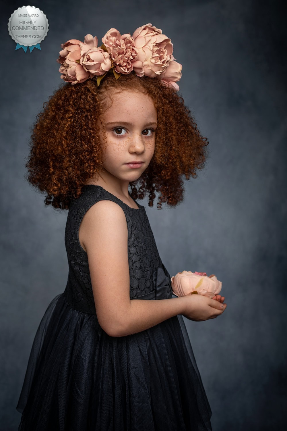 Young girl with curly red hair holds pink flower in hands and has some on her hair stares back into camera.