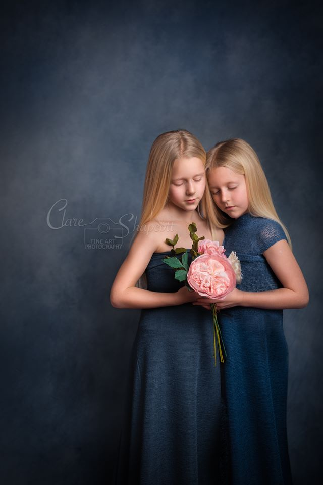Identical twin sisters in blue dresses both hold pink flowers in front of blue background.