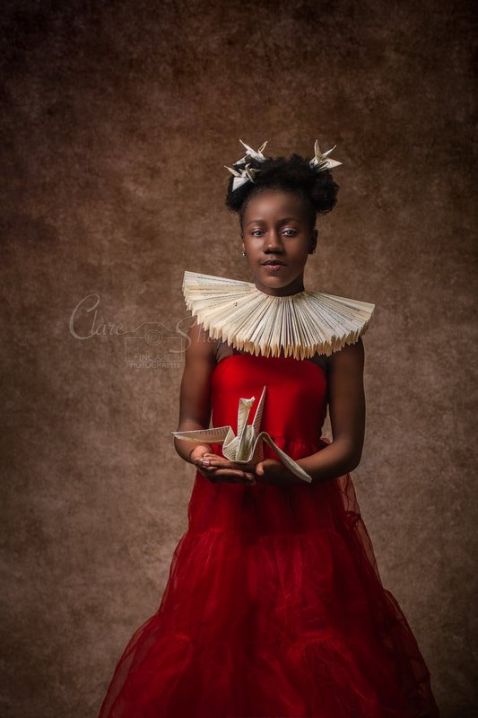 Young girl in red dress has origami cranes in her hands and hair and wears paper ruff around neck.