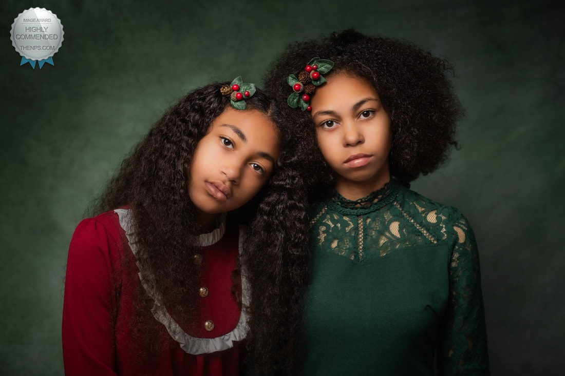 Fine art photo of two girls in red and green dress and long brown curly hair lean against each other and face camera.