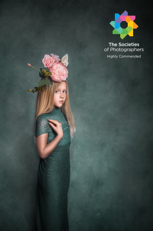 Award winning photograph of a young girl in long green dress holding her shoulder and wearing pink flower accessories on her head.