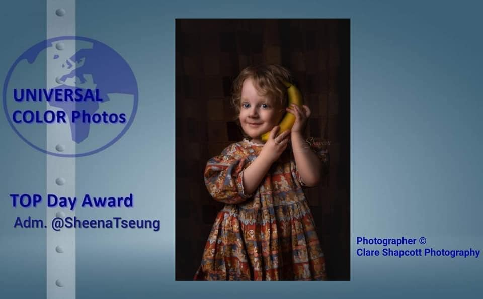 Photograph of young girl wearing teddy bear patterned dress holding banana phone to ear and smiling cheekily.