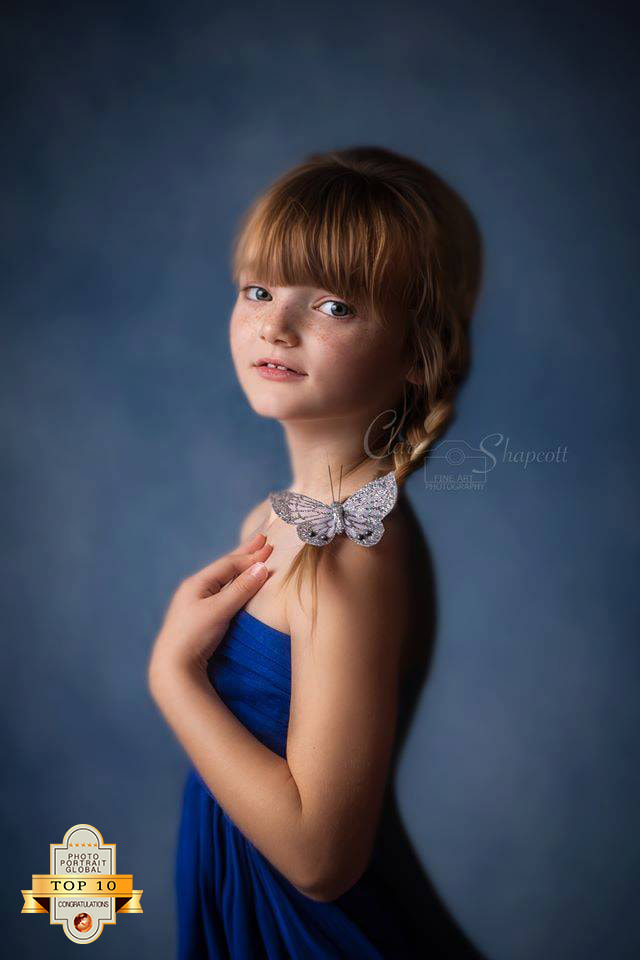 Award winning and published portrait of young girl in blue dress with ponytail touching shoulder and looking at camera.