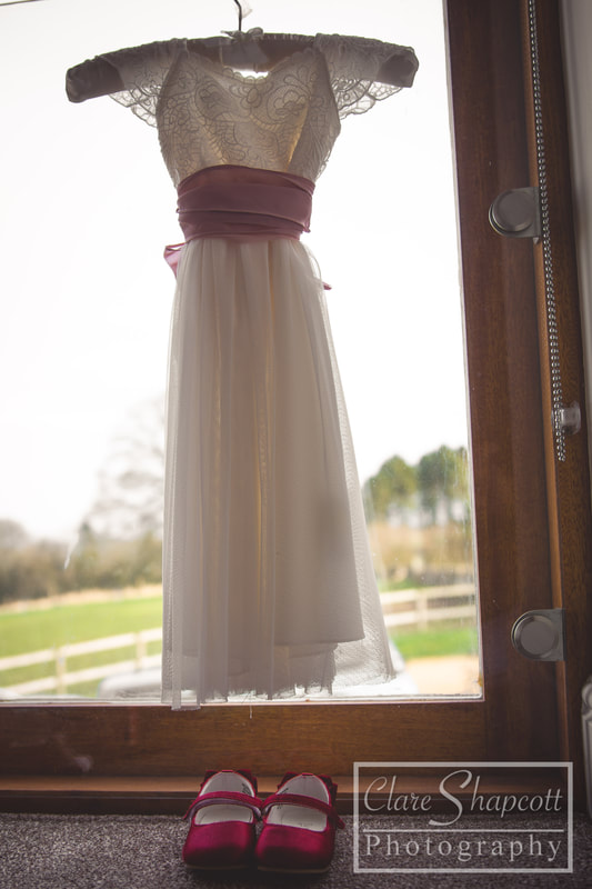 Wedding dress hanging on hook with pink sash by window