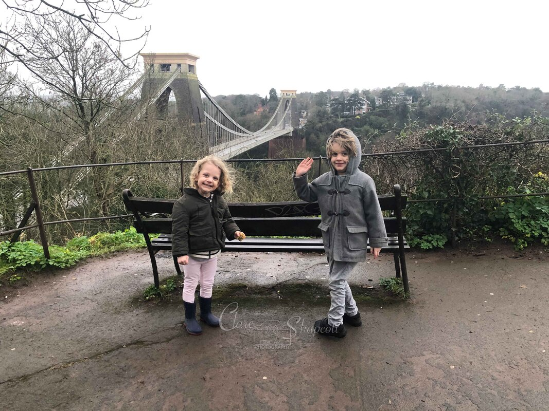 Photograph of baby splashed by sister in summer