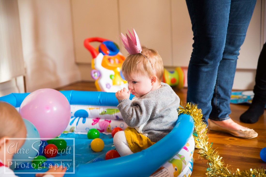 Little girl in ball pit with party hat on