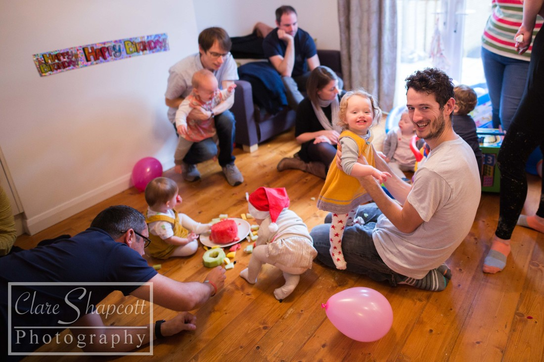 Babies eating and playing and being held at party