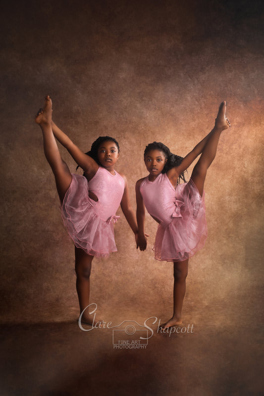 Two young dancing girls wearing pink outfits stretching their legs high up into the air and holding hands.