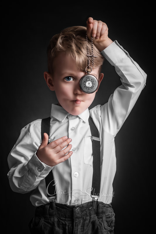 Award winning and published portrait photograph of young boy wearing white shirt and suspenders holding grey pocket watch to eye.