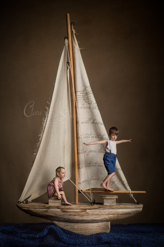 Fine art illustrative photograph of two young children playing on top of their model boat.