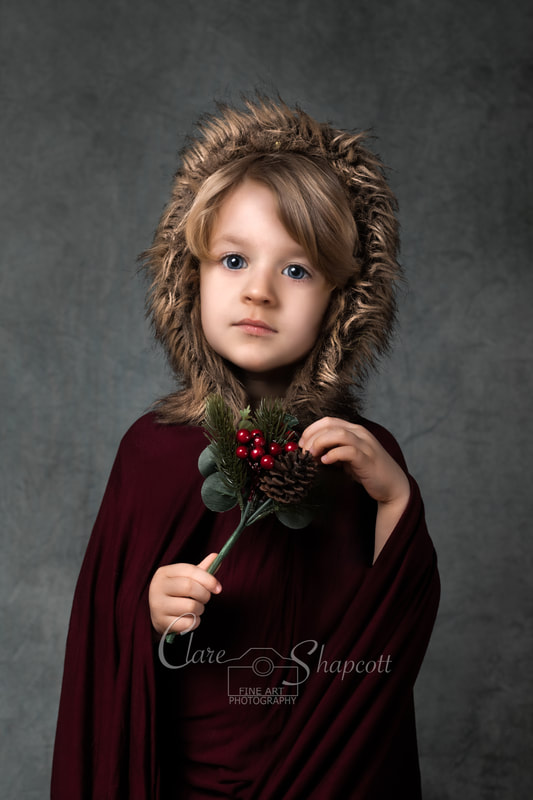 Young boy wearing red cloak holds christmas themed leafy ornament during fine art photoshoot.