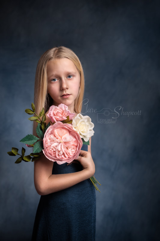 Fine art portrait of young blonde girl in blue dress holding pink and white flowers in front of blue background.