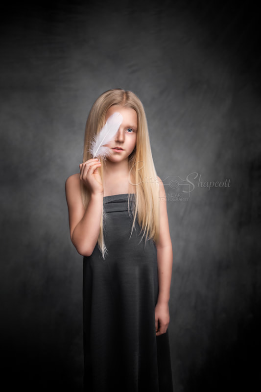 Fine art creative portrait of young blonde girl covering her eye with a white feather.
